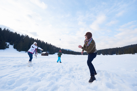 winter park: happy young  family playing in fresh snow  at beautiful sunny winter day outdoor in nature