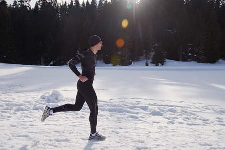 deportistas: young  man jogging on snow in forest, bautiful sunny winter day. handsome sporty ahtlete man running