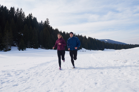 jogging in nature: healthy young couple jogging outside on snow in forest. athlete running on  beautiful sunny winter day Stock Photo