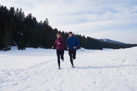 people jogging: joven pareja sana trotar al aire libre en la nieve en el bosque. atleta corriendo en hermoso día soleado de invierno