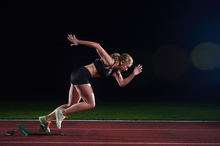 fast track: pixelated design of woman  sprinter leaving starting blocks on the athletic  track. Side view. exploding start Stock Photo