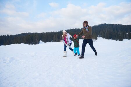 young  family: happy young  family playing in fresh snow  at beautiful sunny winter day outdoor in nature