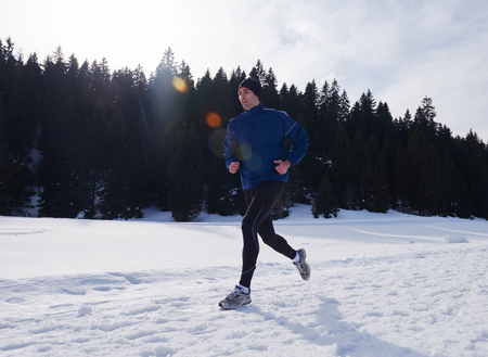 individual sport: young  man jogging on snow in forest, bautiful sunny winter day. handsome sporty ahtlete man running