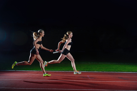 staffel: Frau sportliche Läufer vorbei Taktstock in Staffellauf Lizenzfreie Bilder