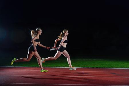 carrera de relevos: mujer corredores de atletismo que pasan el bast�n en carrera de relevos Foto de archivo
