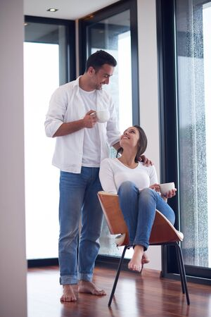 woman window: relaxet young couple drink first morning coffee  over big bright window in moder home villa interior