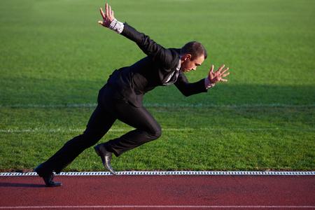 Geschäftsmann in der Anfangsstellung betriebsbereit zu laufen und sprinten auf Leichtathletik Rennbahn