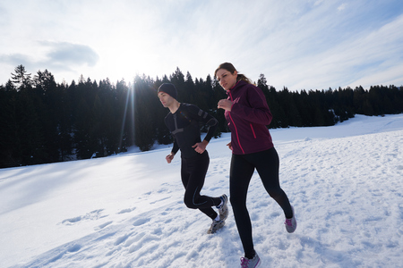the athlete: healthy young couple jogging outside on snow in forest. athlete running on  beautiful sunny winter day Stock Photo