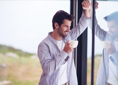 relajado: joven relajado beber primer café de la mañana en la casa moderna en el interior en la ventana de lluvias cae por la ventana Foto de archivo