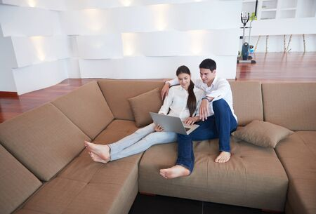 women sitting: happy young relaxed  couple working on laptop computer at modern home interior