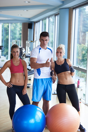 group portrait of healthy and fit young people in fitness gym photo
