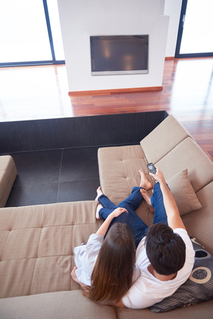 pareja viendo television: Relaxed young couple watching tv at home in bright living room