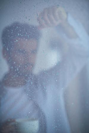uomo sotto la pioggia: rilassato giovane bere primo caffè del mattino a casa moderna chiuso alla finestra finestra piovosa scende Archivio Fotografico