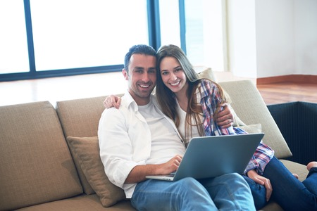 couple couch: happy young relaxed  couple working on laptop computer at modern home interior