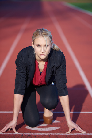 business woman in start position ready to run and sprint on athletics racing track Stock Photo