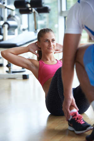 young sporty woman with trainer exercise in fitness gym photo