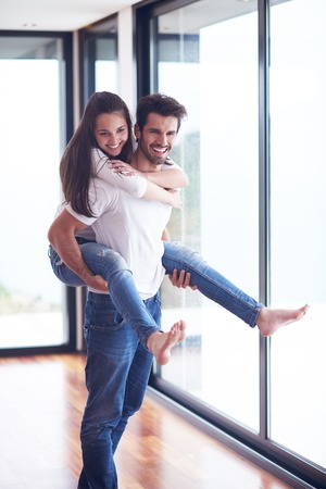 familias felices: feliz pareja romántica joven divertirse relaje sonreírle interior moderno salón hogar