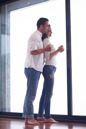 windows: relaxet joven pareja beber primer café de la mañana sobre gran ventana brillante en moder interior villa casa