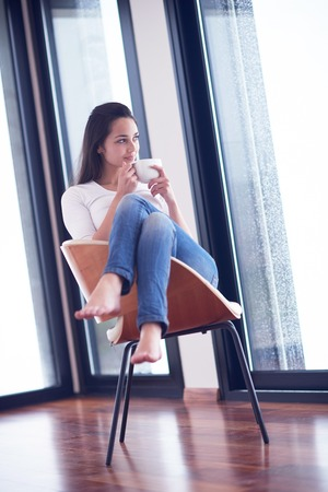 woman window: beautiful young woman drink first morning coffee at modern home interior with rain drops on big window door glass Stock Photo