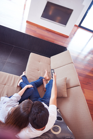 couple watching tv: Relaxed young couple watching tv at home in bright living room