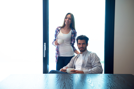 young happy couple: relaxet young couple drink first morning coffee  over big bright window in moder home villa interior
