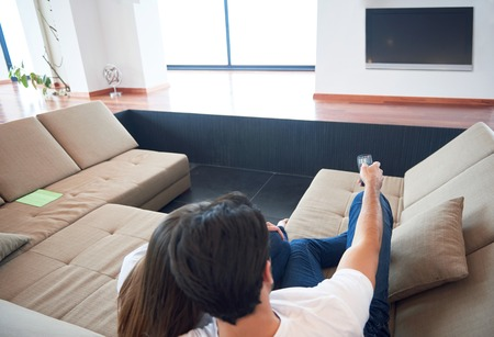 sofa television: Relaxed young couple watching tv at home in bright living room
