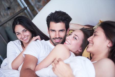 young couple sex: Молодой мачо плейбой красивый мужчина в постели с тремя красивая сексуальная женщина
