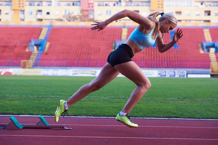 sprinter: pixelated design of woman  sprinter leaving starting blocks on the athletic  track. Side view. exploding start Stock Photo