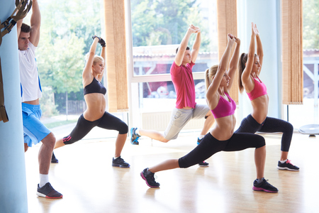 Group of people exercising at the gym and stretching photo