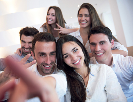 young adult man: group of friends taking selfie photo with tablet at modern home indoors Stock Photo