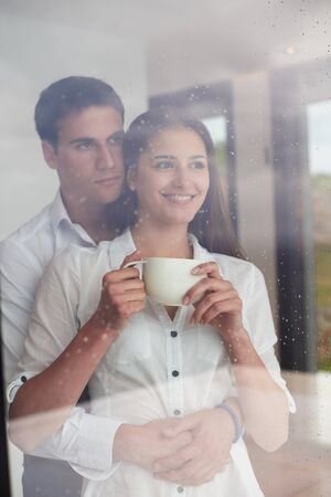 drink coffee: relaxet young couple drink first morning coffee  over big bright window in moder home villa interior