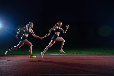 mujer corredores de atletismo que pasan el bastón en carrera de relevos