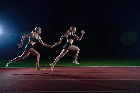 pista de atletismo: mujer corredores de atletismo que pasan el bastón en carrera de relevos Foto de archivo