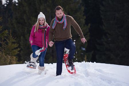 glückliches junges Paar, die Spaß und Wandern in Schneeschuhen. Romantische Winterruheszene