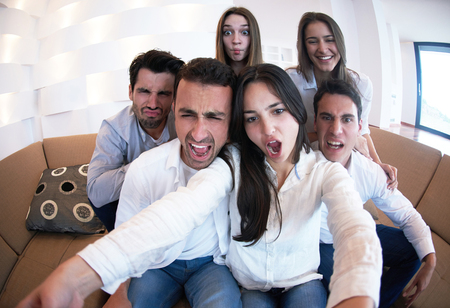 group of friends: group of friends taking selfie photo with tablet at modern home indoors Stock Photo