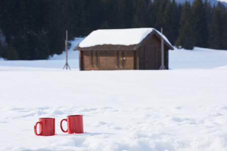 hot drink: two red coups of hot tea drink in snow at beautiful winter  sunny day scene with wooden house in background in forest