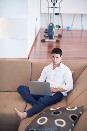 trabajando en casa: apuesto hombre de negocios en ropa casual trabajando en equipo portátil de casa y tomar un café por la mañana abetos