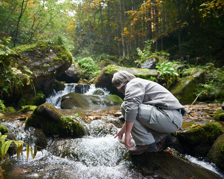 spring water: hiking in beautiful nature, man drink fresh water from spring