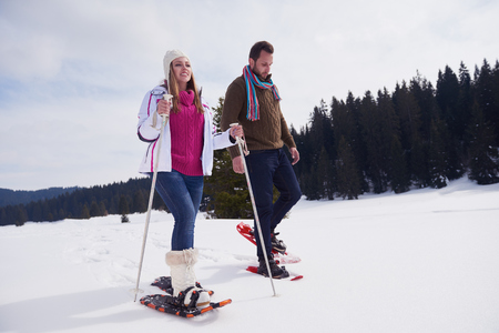 romantic couple: happy young  couple having fun and walking in snow shoes outdoor in nature at beautiful winter day. Health sport and relaxation Stock Photo