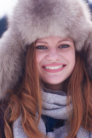girl in a hat: portrait of beautiful young redhair woman in snow scenery with warm hat Stock Photo