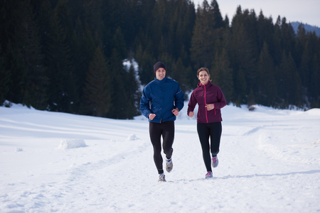 ropa deportiva: healthy young couple jogging outside on snow in forest. athlete running on  beautiful sunny winter day Foto de archivo