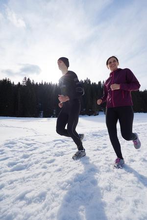 ropa deportiva: joven pareja sana trotar al aire libre en la nieve en el bosque. atleta corriendo en hermoso día soleado de invierno