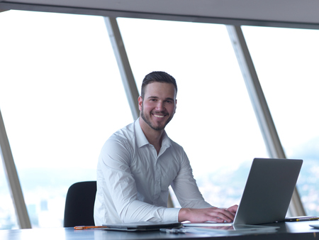 happy young business man work and relax at modern bright office interior, hipster with beard at workplace Stock Photo