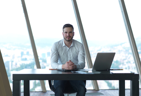 using tablet: happy young business man work and relax at modern bright office interior, hipster with beard at workplace Stock Photo