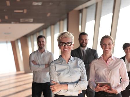 gente reunida: grupo de personas de negocios de pie juntos como equipo por la ventana en el moderno interior de la oficina brillante Foto de archivo