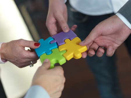 red puzzle piece: business people group assembling jigsaw puzzle and represent team support and help concept, top view at modern office interior Stock Photo