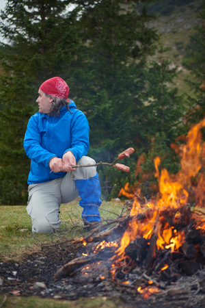 barbecues: hiking man prepare tasty sausages on campfire in mountains