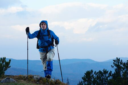 outdoor sport: advanture man with backpack hiking on mountain forest Stock Photo