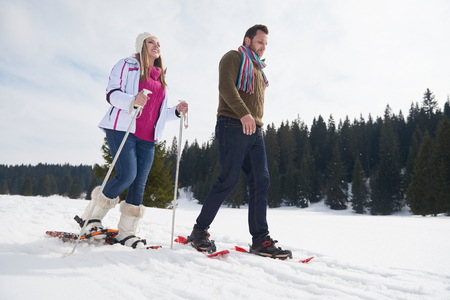couple nature: happy young  couple having fun and walking in snow shoes outdoor in nature at beautiful winter day. Health sport and relaxation Stock Photo
