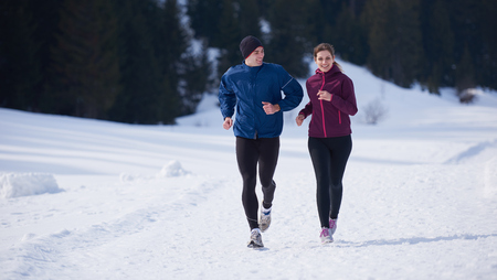 sunny: healthy young couple jogging outside on snow in forest. athlete running on  beautiful sunny winter day Stock Photo